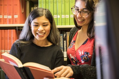 Students in Foster Business Library stacks