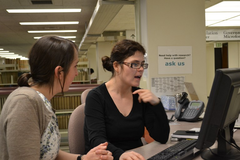 Anna Bjartmarsdottir helps a patron with a reference question at Allen Library