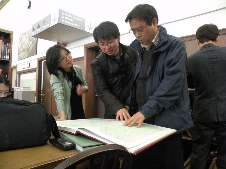 Hyok Young Yee assists patrons with an oversized book in the Beckmann Reading Room of the East Asia Library