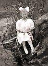Girl sitting beside a stream