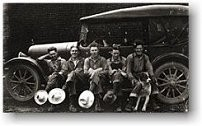 Mill workers sitting on running board of a car