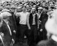 Tacoma and Seattle longshoremen lead a strikebreaker, identified as 'Iodine' Harradin, off the Seattle docks. Harradin and other strikebreakers were removed under a flag of truce as police stood back. The striker with right arm upraised is Phil Green, Seattle. Port of Seattle photo. Ronald E. Magden Collection.